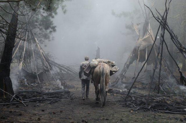 slow-west-2015-006-back-shot-man-with-horse-enter-burnt-village